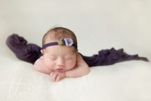 Newborn baby head on hands pose.