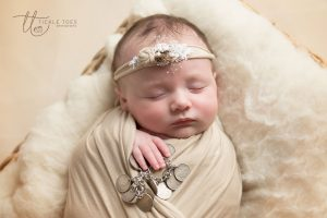 Newborn baby photographer baby holding family heirloom bracelet