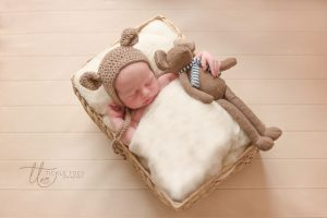 Newborn photography baby in bed with teddy